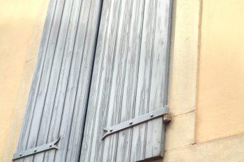 Volet gris-bleu sur une façade ocre • Photo Volet en bois Libre de droit / Image de décoration urbaine typique du Béarn - Creative Lune : Banque d'images